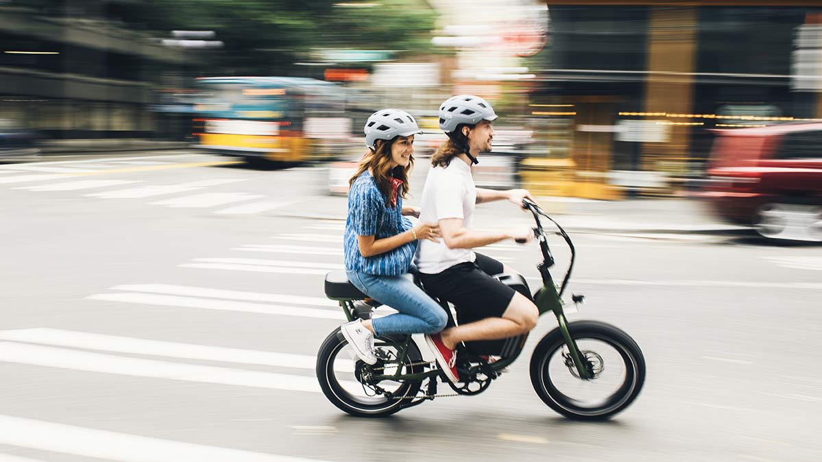 Two people riding a Rad Power Bike Runner1 Utility Cargo e-bike