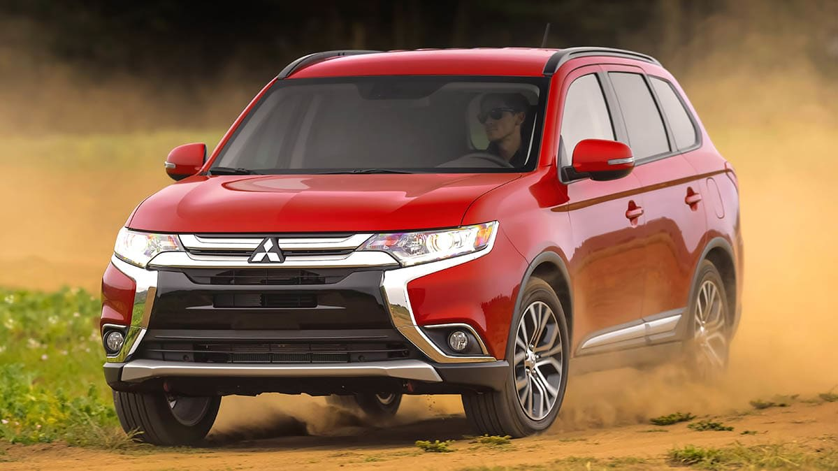 A 2016 Mitsubishi Outlander SUV—a vehicle that is subject to a recall—driving on sand