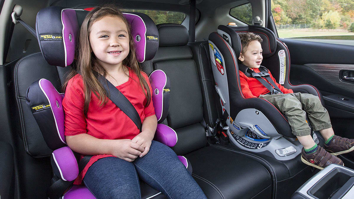 A young girl (left) and a young boy (right), each sitting in a car seat