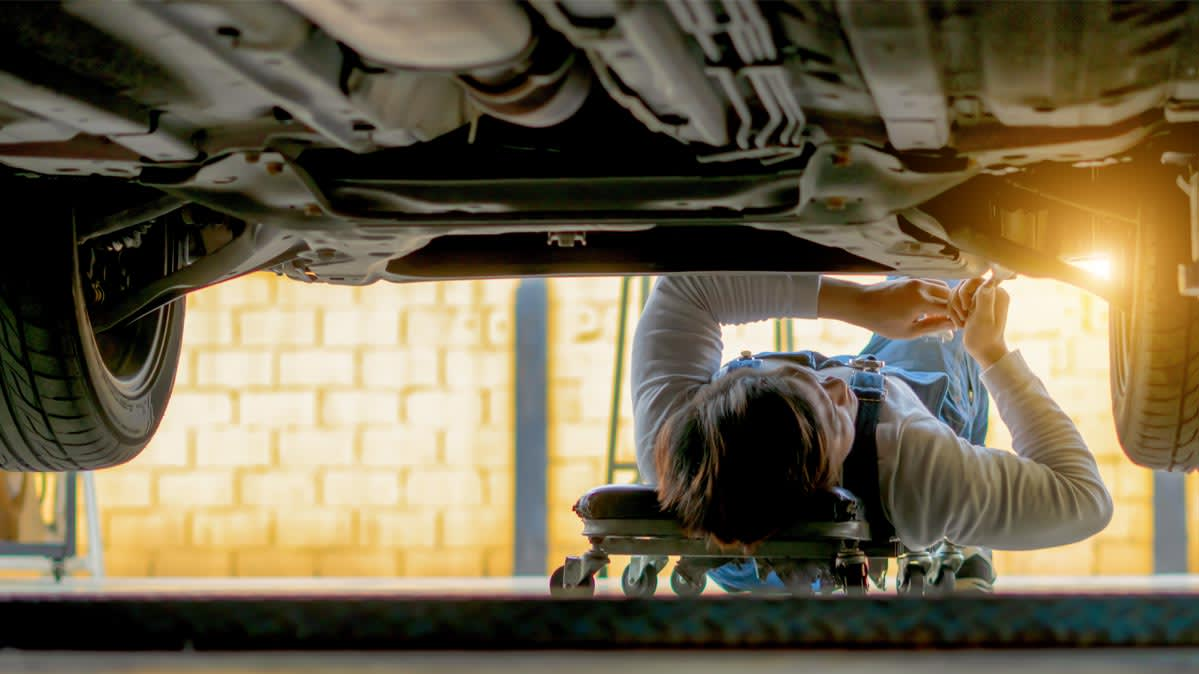 A car mechanic checking the underbody of a car