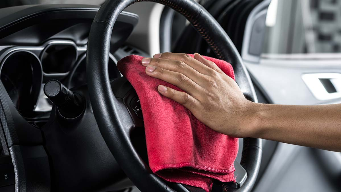A person disinfecting a car interior