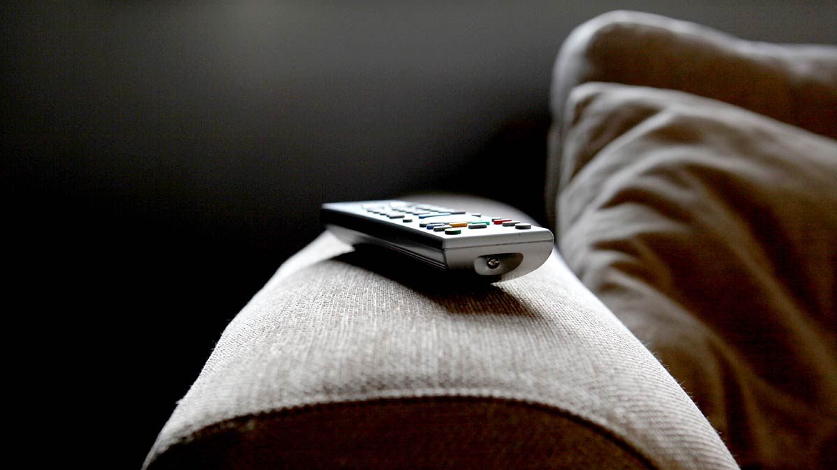 A TV remote resting on the arm of a couch.