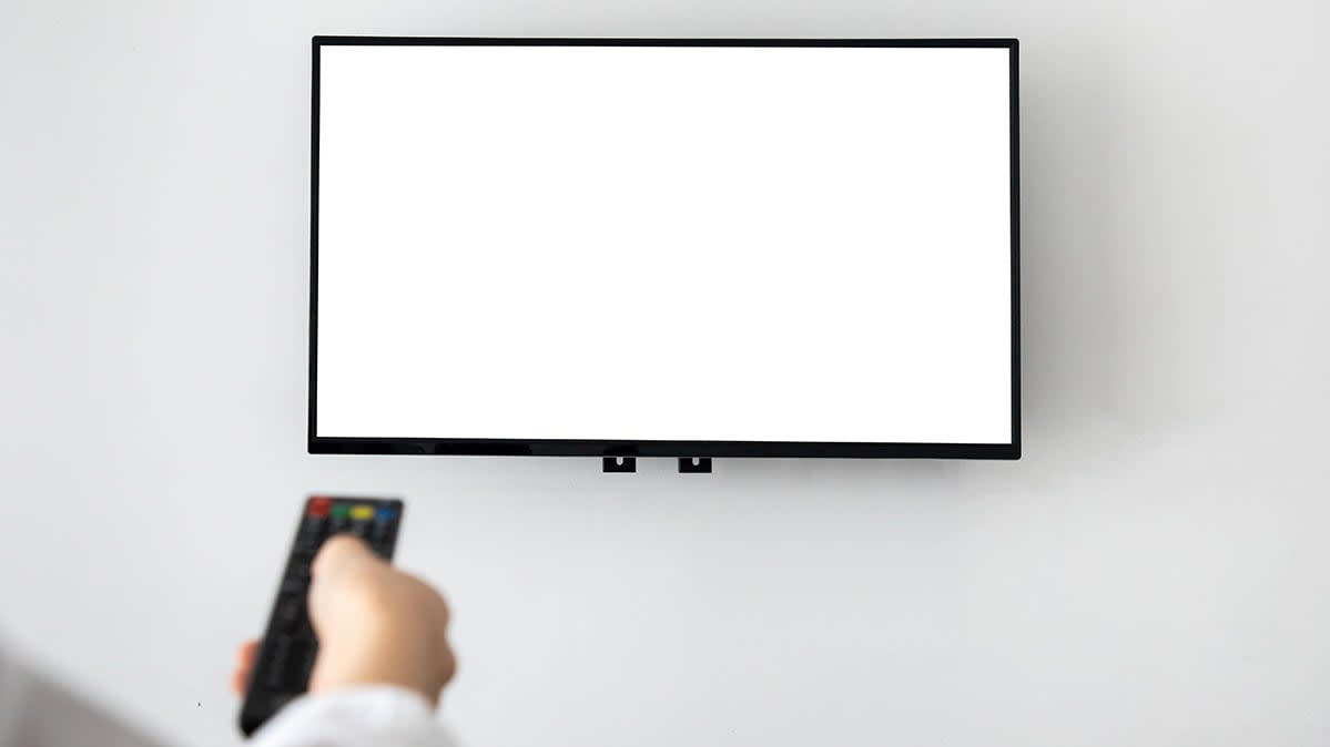Hand of a television viewer with a remote control aimed at a blank, wall-mounted, brand-free flat screen