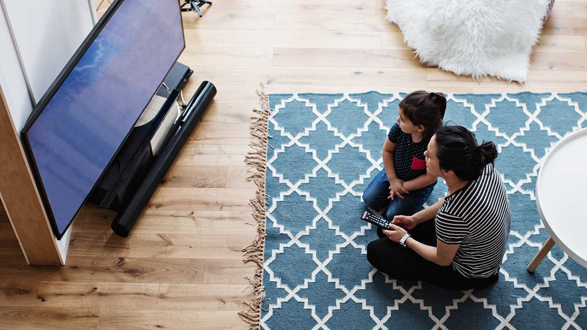 Picture of a woman and her child using a remote control while watching TV.