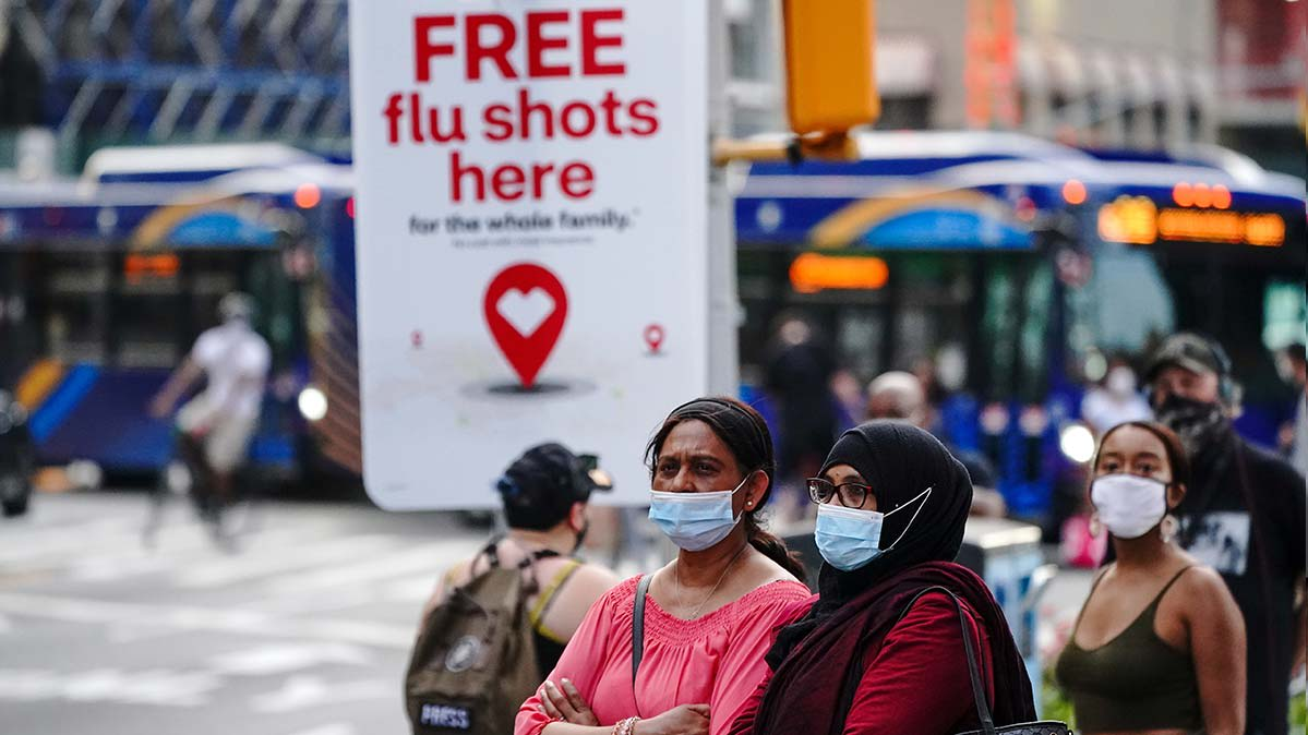 Several pedestrians wearing masks in front of an advertisement for flu shots.