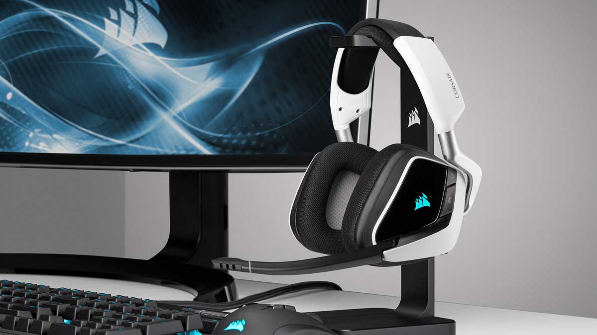 A pair of gaming headsets next to a computer screen.