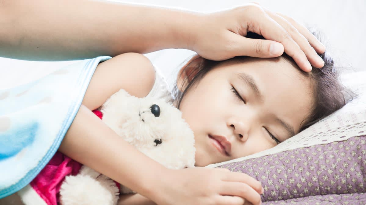 An image of a sleeping child with a hand on her forehead.
