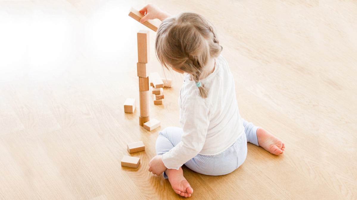 A small child on the floor plays with wooden blocks