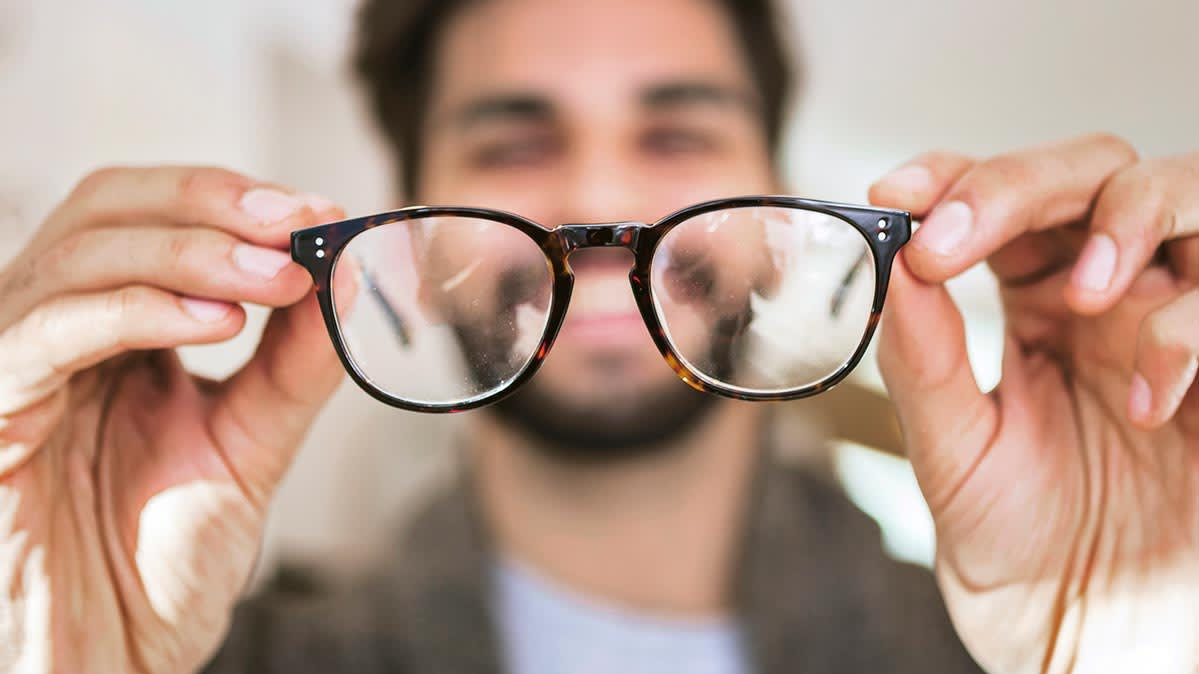 A smiling man examining a pair of eyeglasses