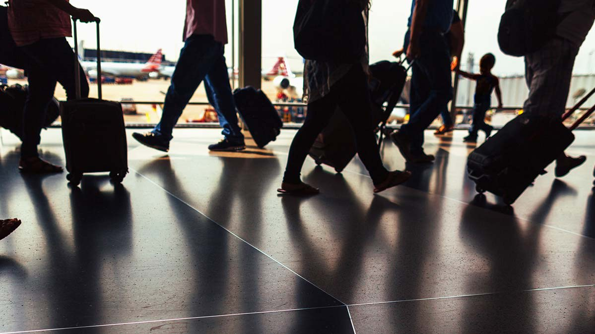 Photo showing people walking through an airport with their luggage