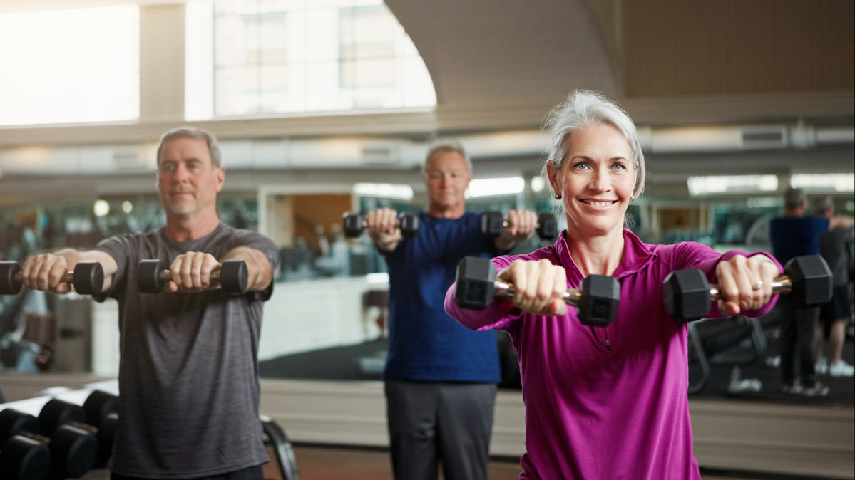 Older adults lifting weights in a class to help maintain strength as they age.