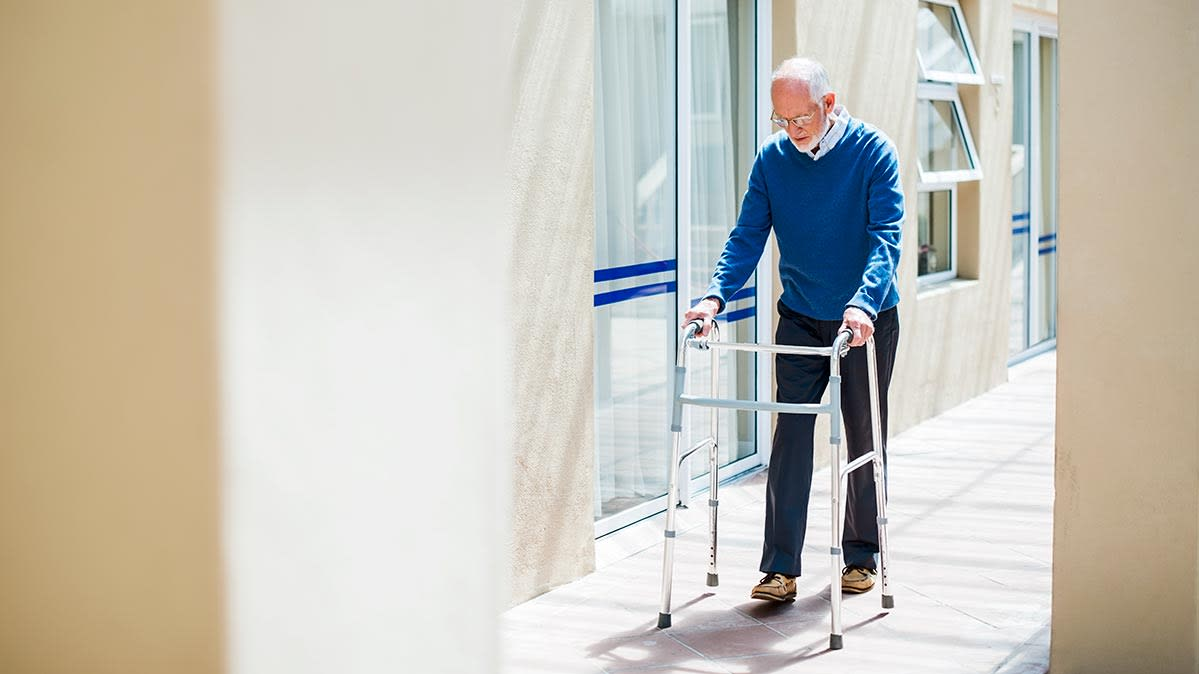 An older man using a walker on the sidewalk outside a long-term-care facility.