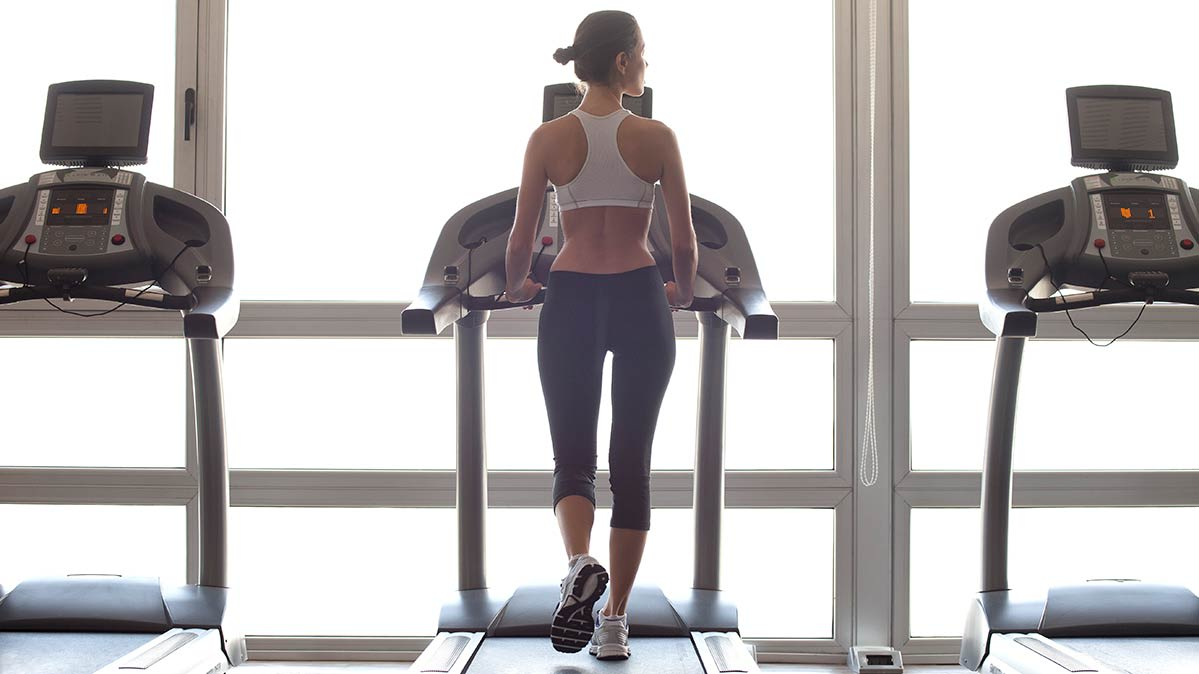 A woman works out on a treadmill, with two empty treadmills next to her