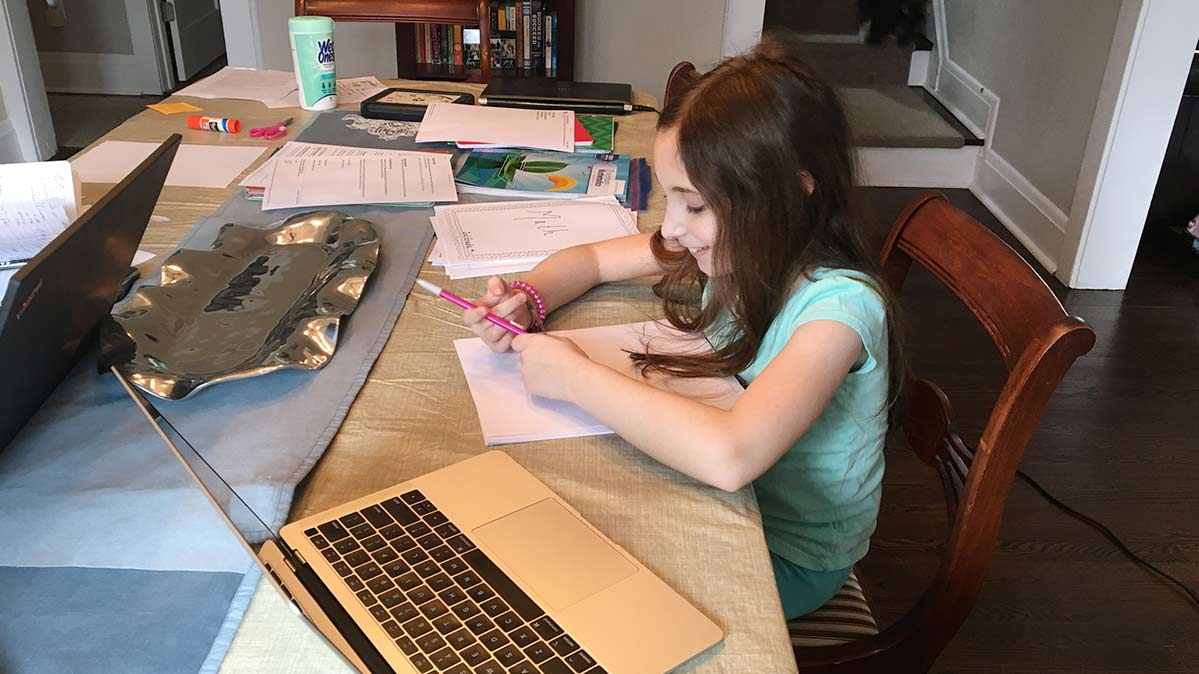 Kid sitting at the dining room table with a laptop and drawing paper.