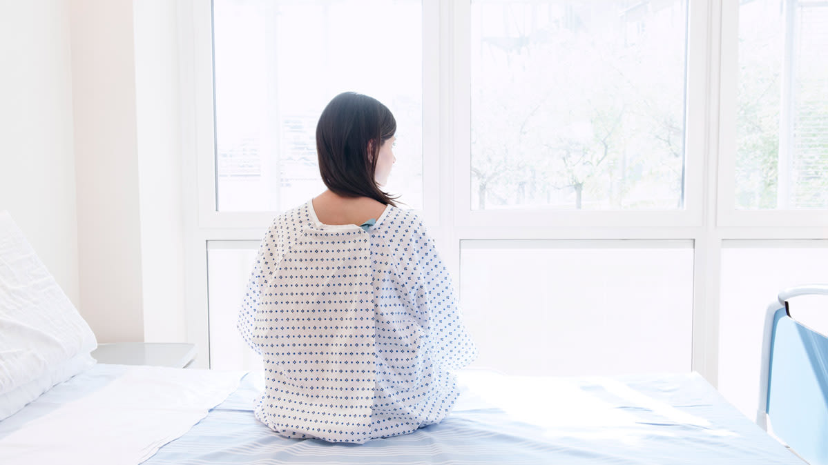 A patient in a hospital gown sitting on the edge of a hospital bed facing a window