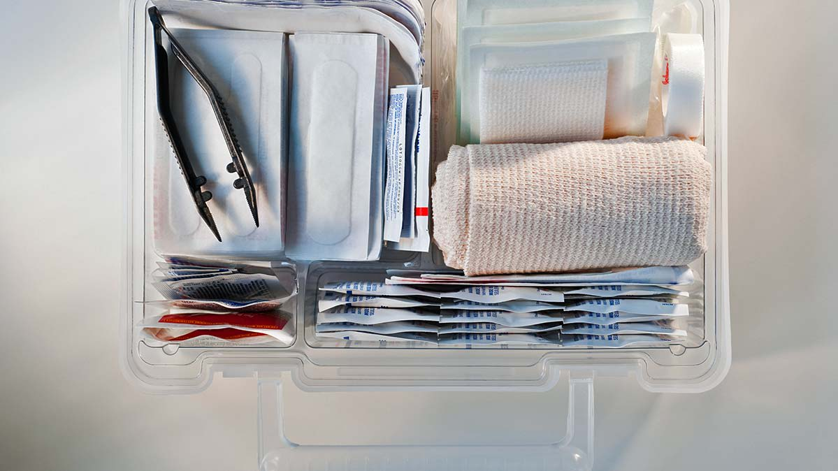 An open first aid kit, showing rolled bandages, bandages in packages, tweezers, and other supplies.
