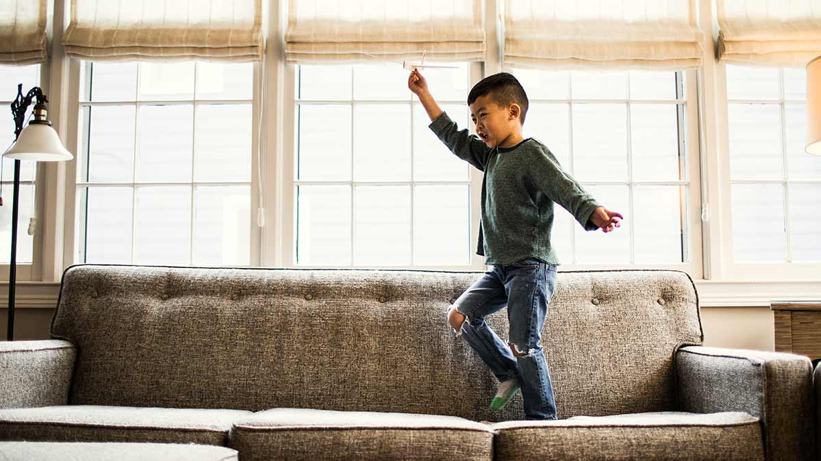 A young boy walking across a sofa in a living room