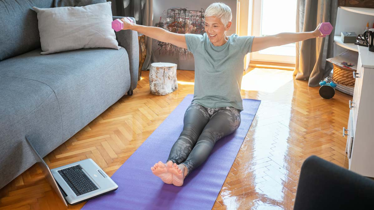 A woman with short gray hair sitting on a yoga mat holding two pink handweights.