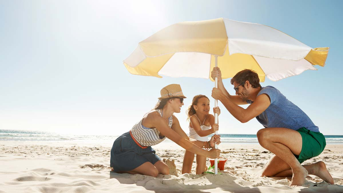 Family on the beach under a sun umbrella