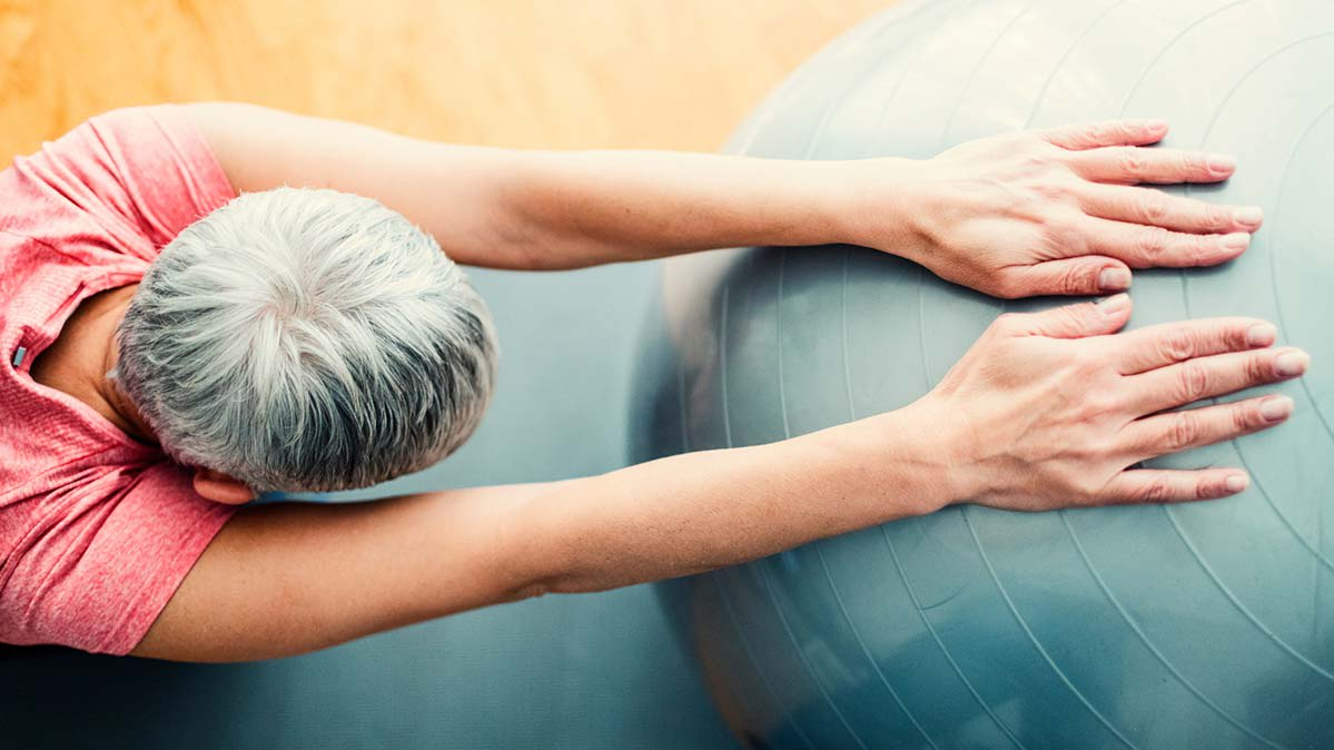 A woman in a downward pose presses her palms against a large exercise ball.