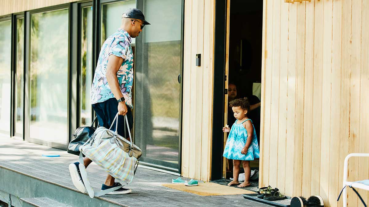 A man carries bags into a vacation rental while a young girl waits at the door.