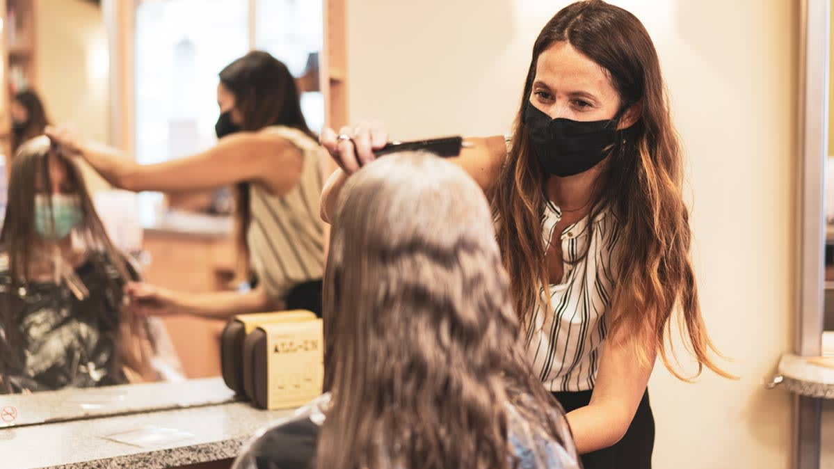 A hair stylist wears a mask as she provides a haircut during the pandemic to a client also wearing a mask