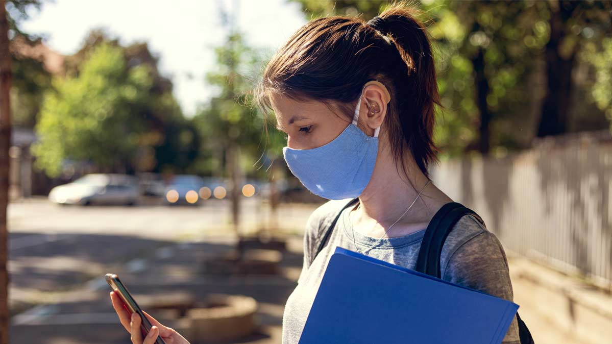 A woman wearing a mask and a hearing aid looking at her smartphone.