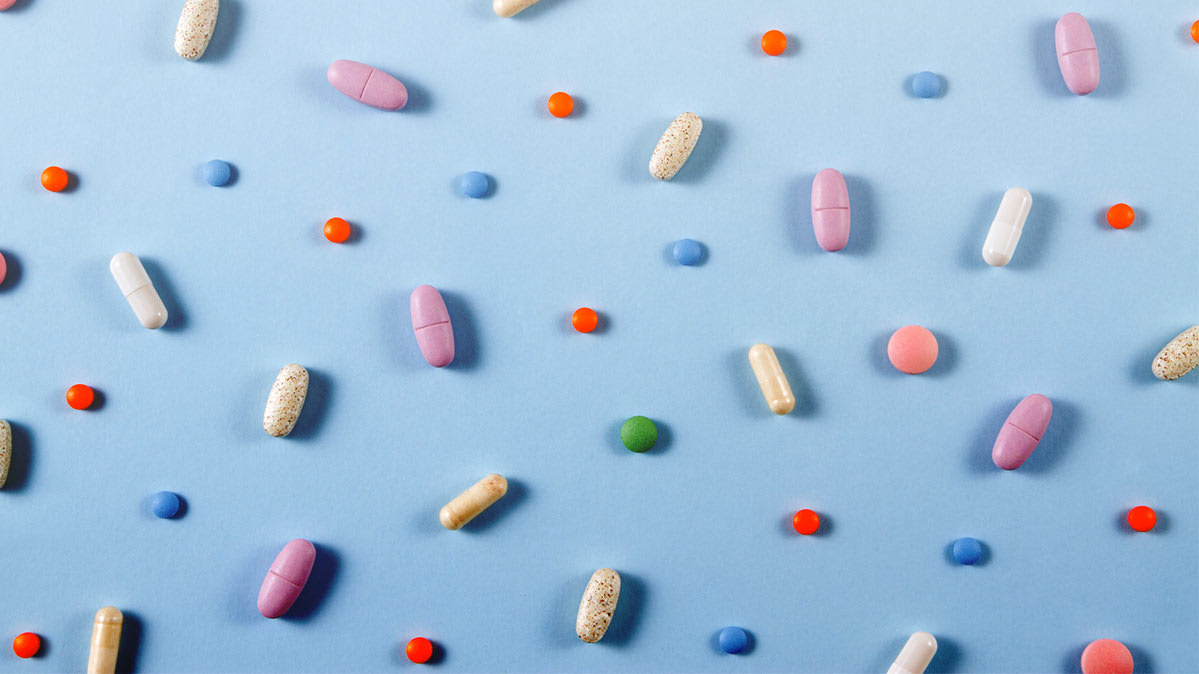 A variety of multicolored pills and capsules on a light-blue surface
