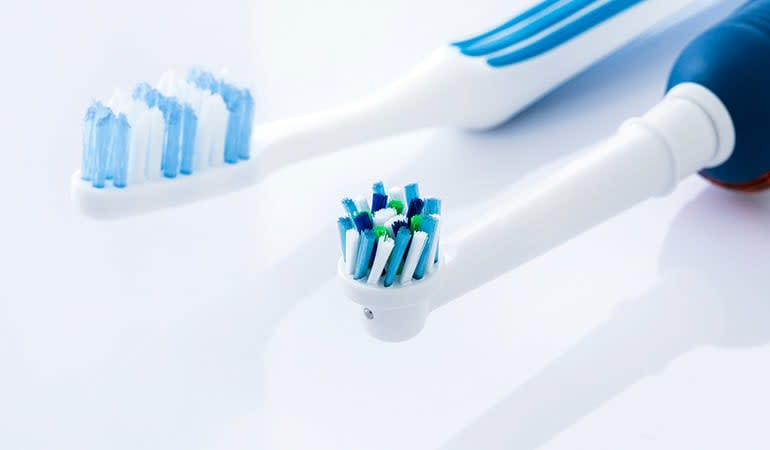 An electric toothbrush and a regular toothbrush.
