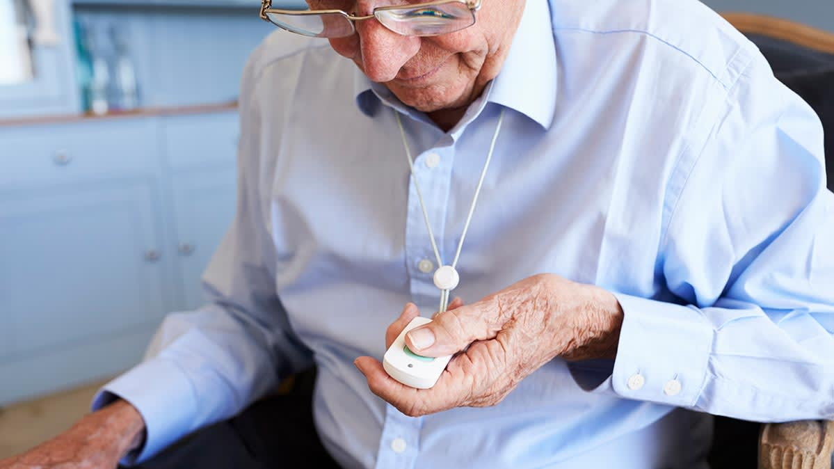 An older person holding a medical alert device.