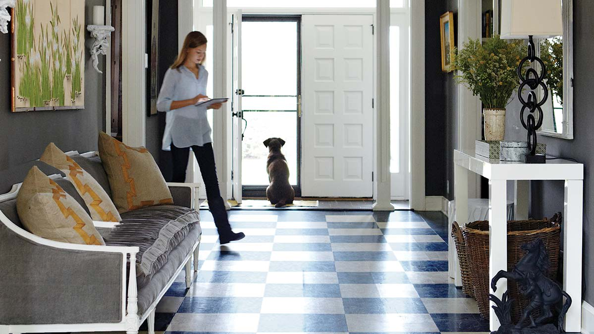 Woman with dog in a front hallway with a checkerboard-patterned vinyl type of flooring