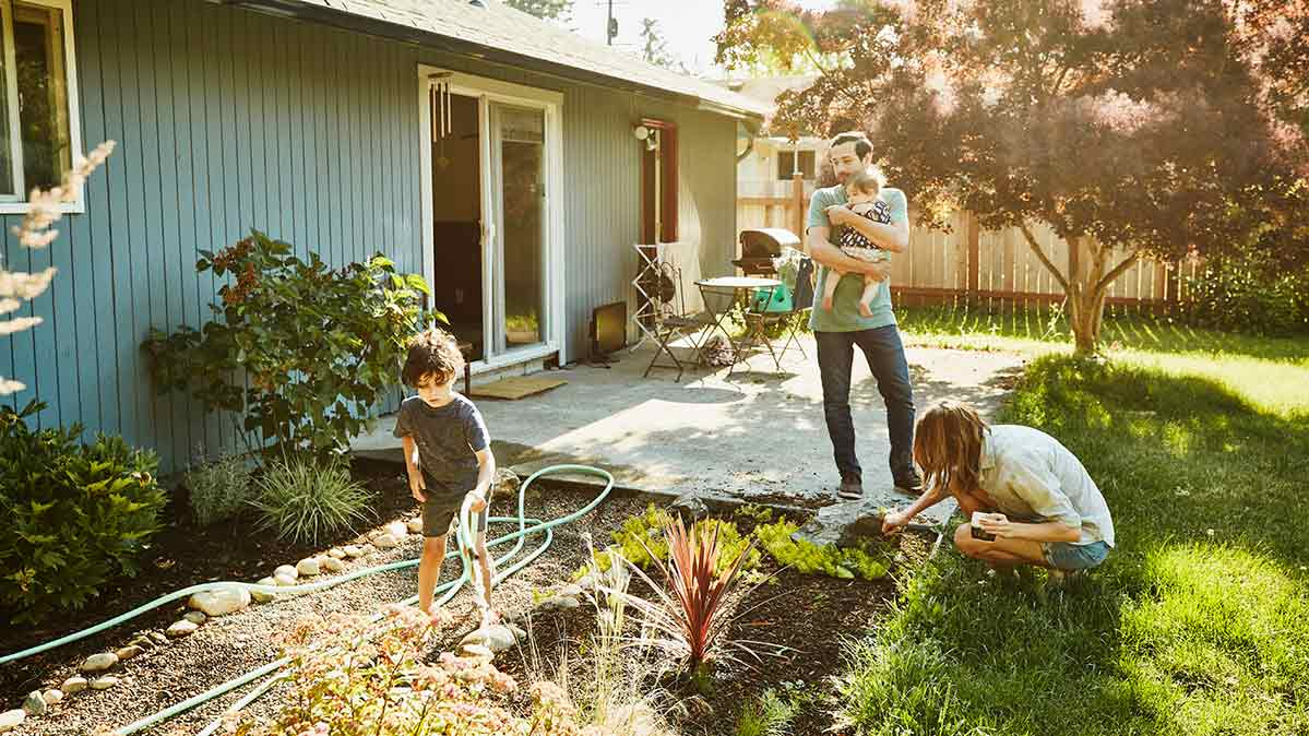 Family with small children sprucing up the yard while they're stuck at home