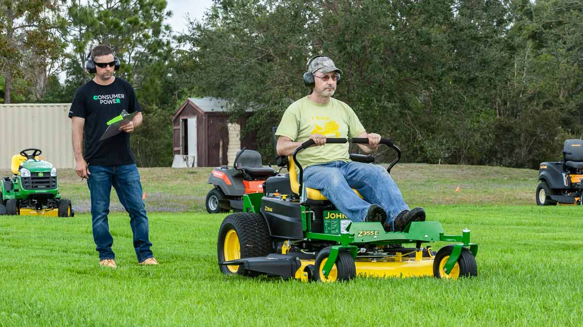 A Consumer Reports tester on a riding mower, with another one behind him with a clipboard.