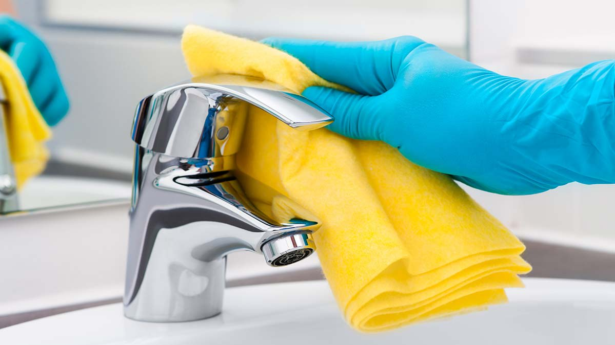 A gloved hand using a disinfectant wipe to clean a faucet.