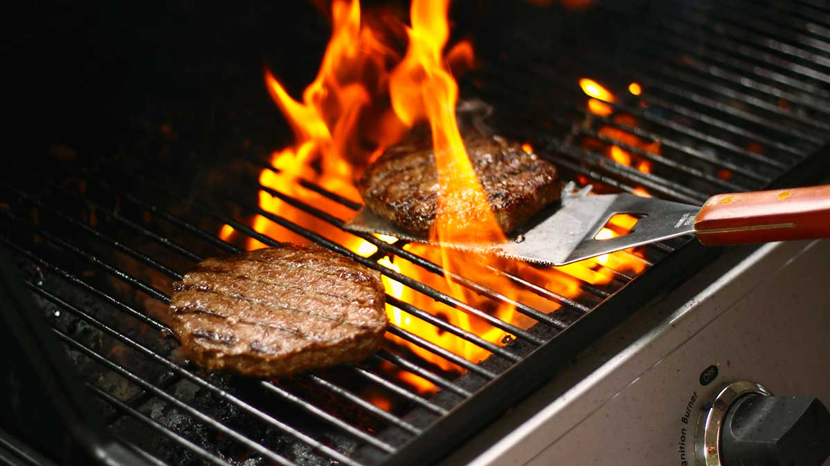 Closeup of 2 burgers cooking on a charcoal grill
