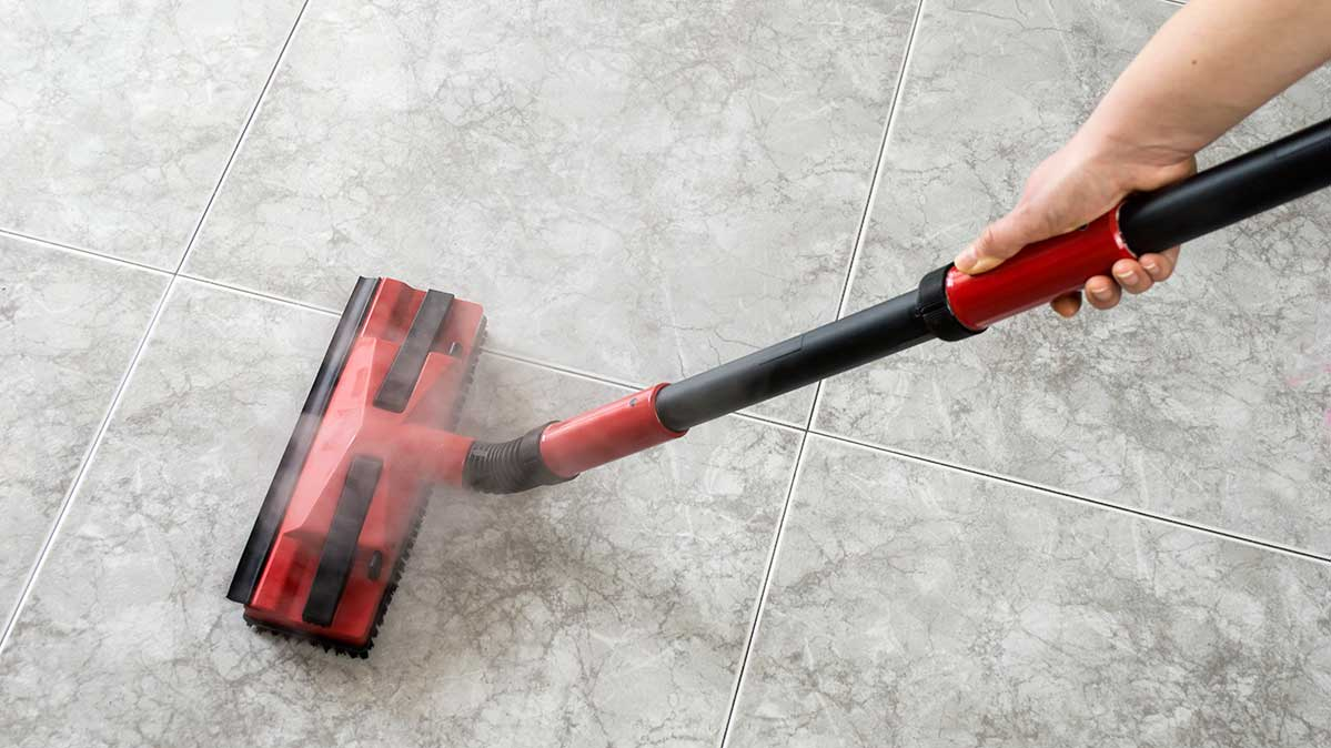 A steam mop releasing steam on tile.