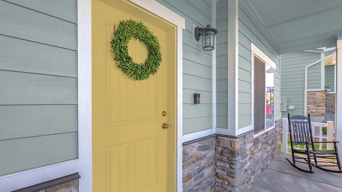 The exterior paint color is a cool neutral and paired with white trim and a yellow door.