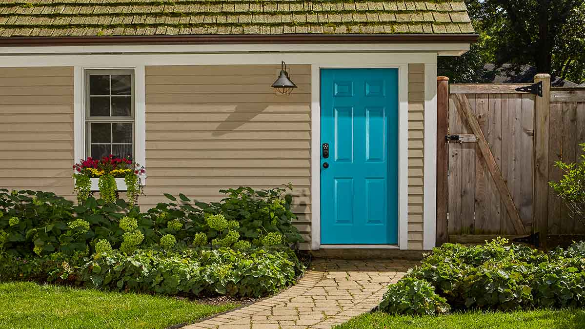 The exterior paint color is a golden neutral, and the front door is a bright blue.