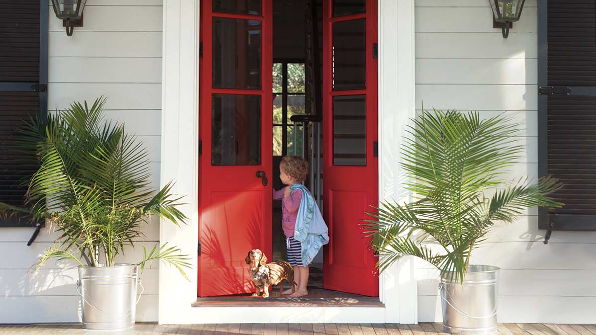 A child and a puppy standing by the red front door of their house.