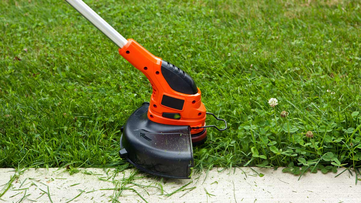 Close-up photo of a string trimmer being used along a walkway