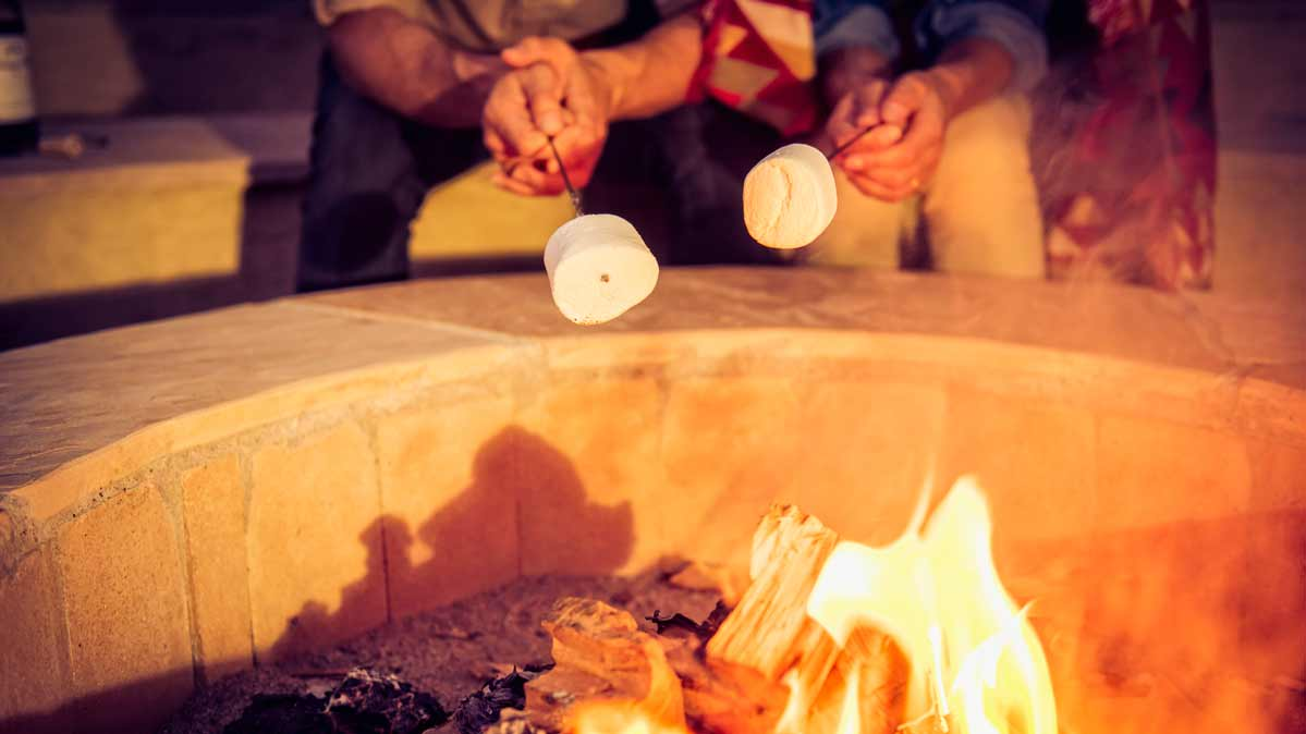 Hands of two seated people roasting marshmallows at a fire pit.