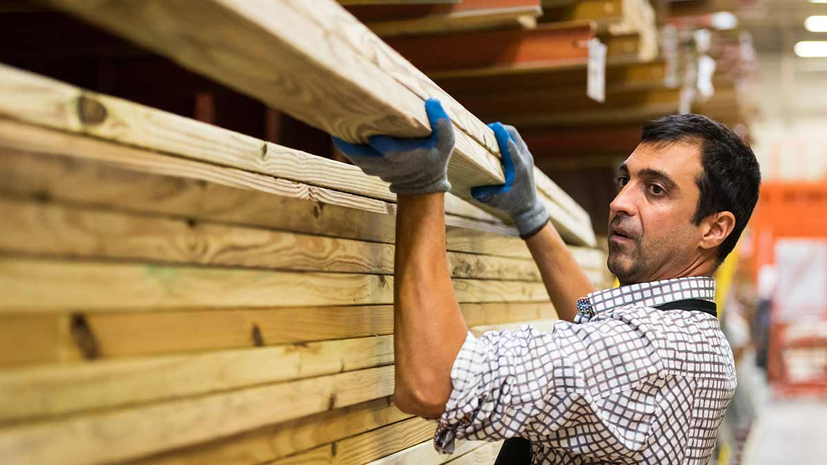 A man placing pressure-treated lumber on shelves at a home center