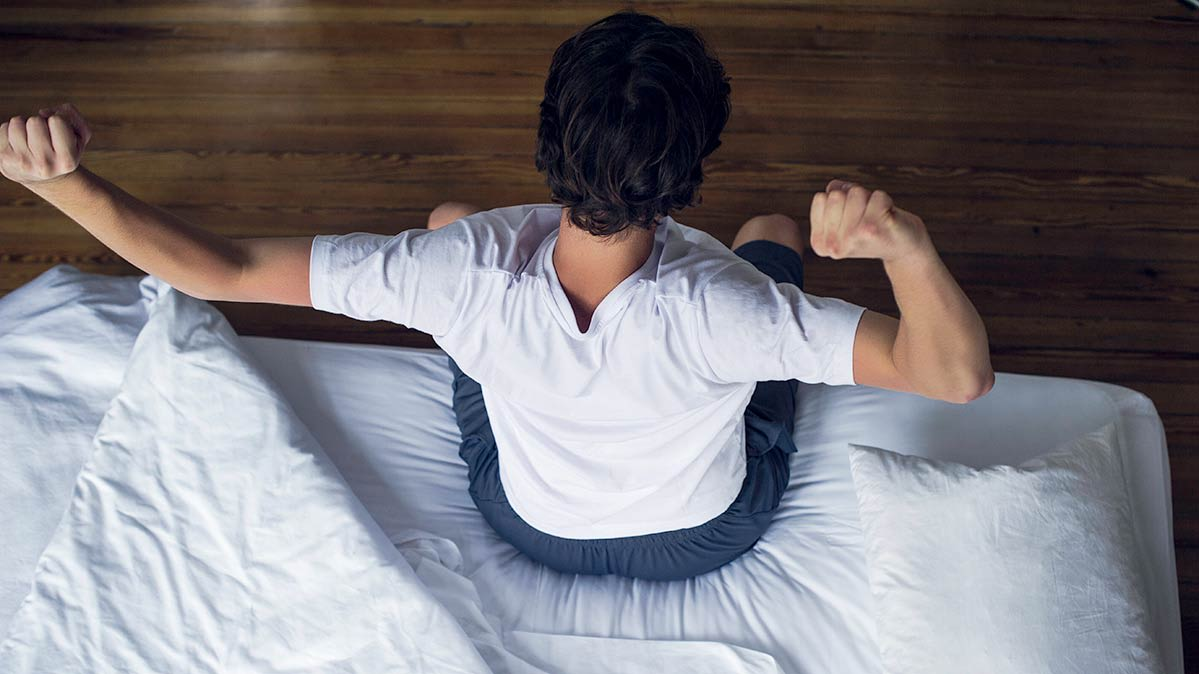 A person stretching while sitting on the edge of a mattress.