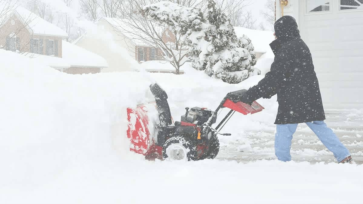 A person using a snow blower to clear a driveway on a wintry day