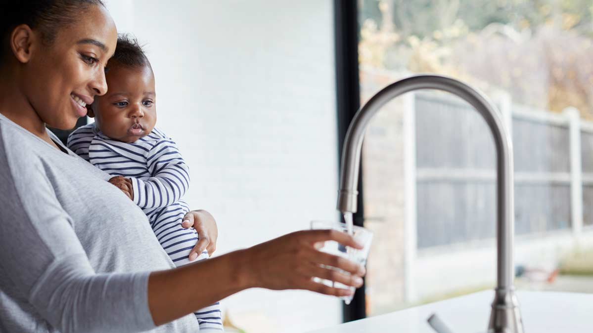 A woman holding a young child filling a glass of water
