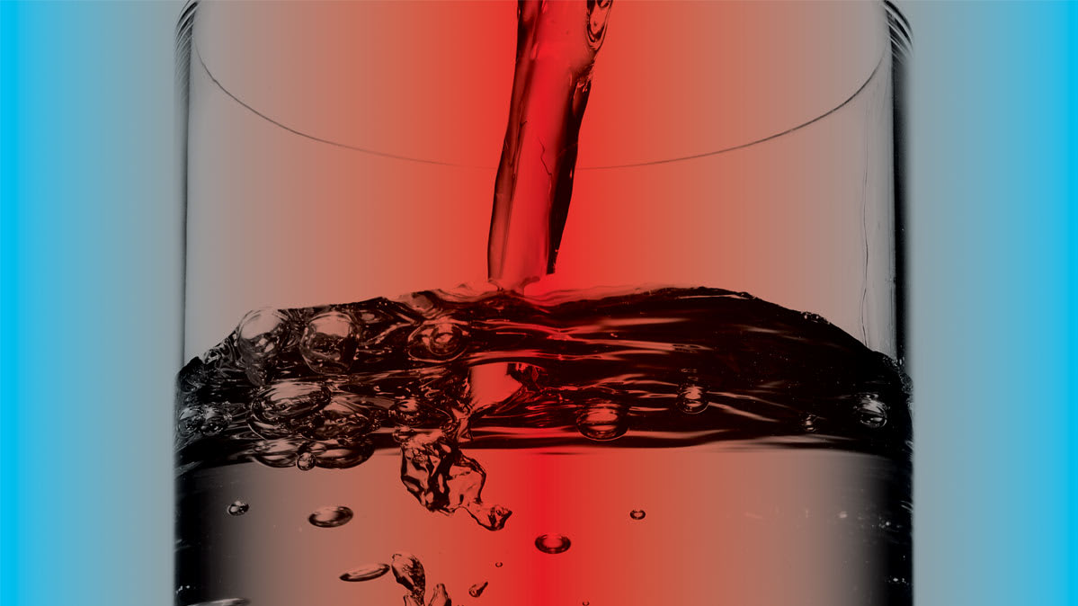 Water being poured into a glass on a red and blue background.