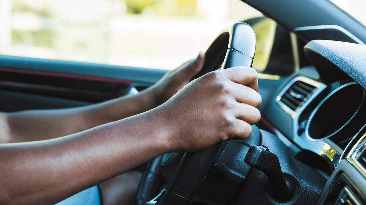 A person holding a car steering wheel with two hands