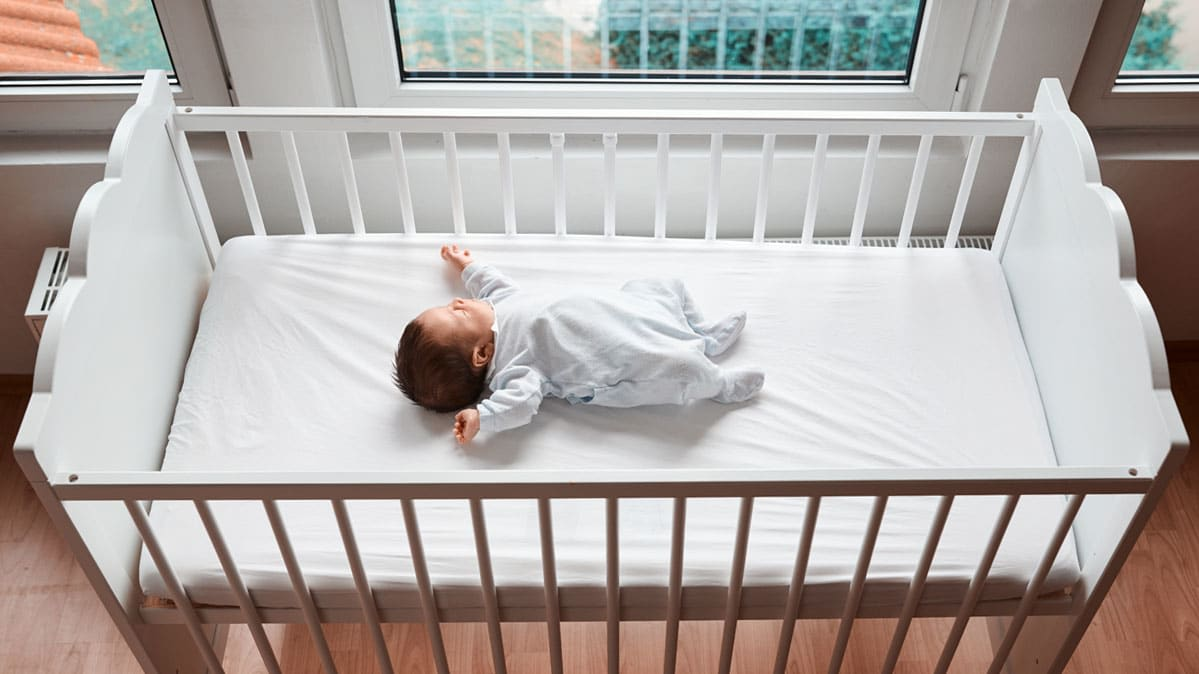 A baby in a crib without bumpers.