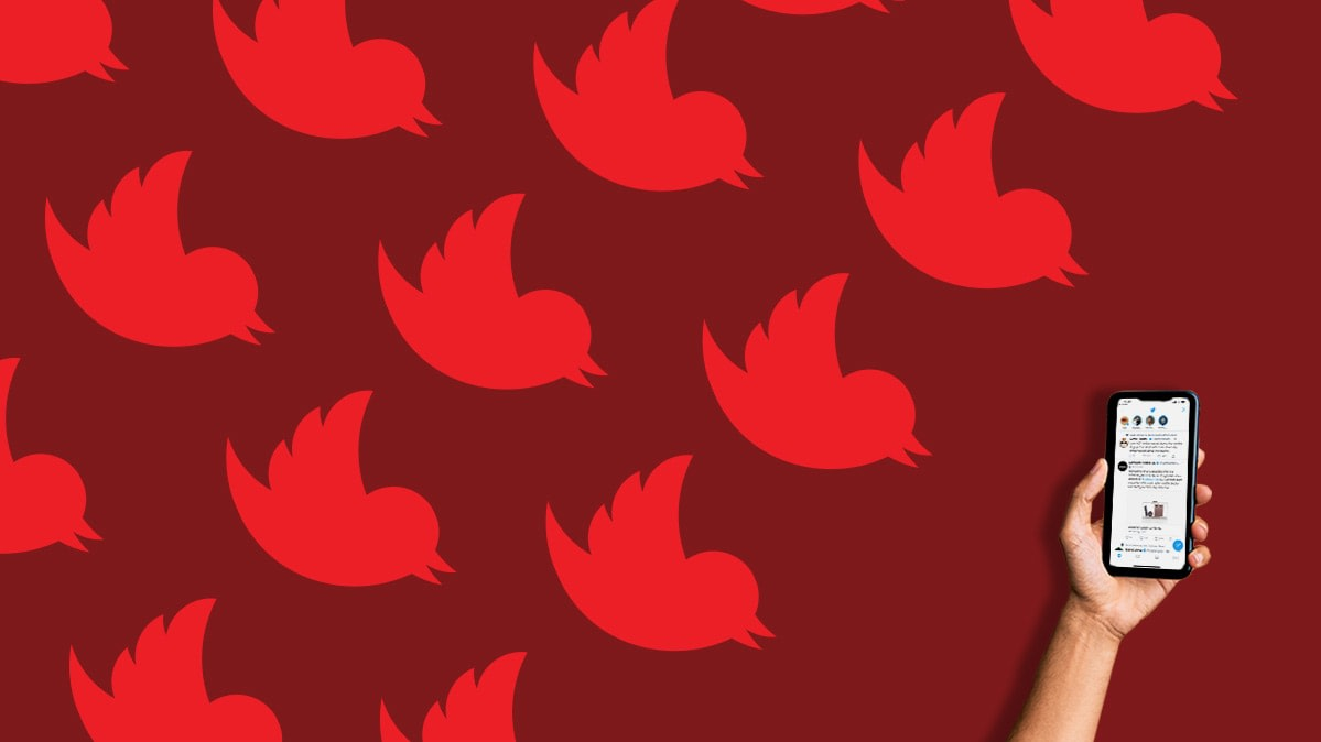 filter out twitter trolls: red Twitter logos and a hand holding a phone