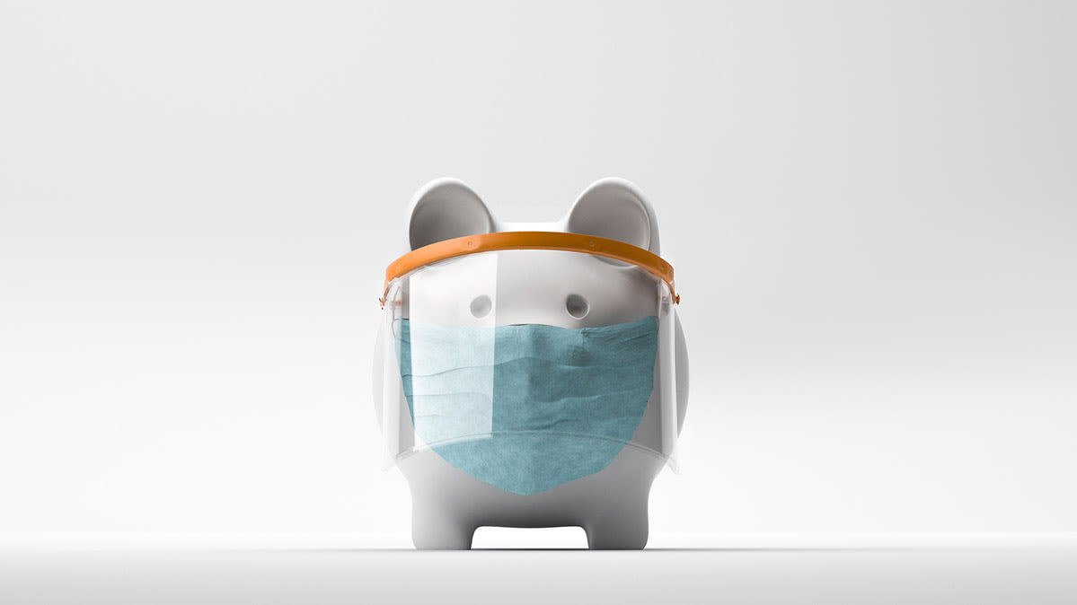 A piggy bank adorned with a face mask and face shield